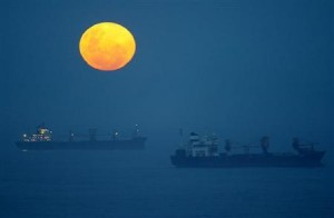 Ships lie at anchor outside the harbour at Durban, as a full moon rises.